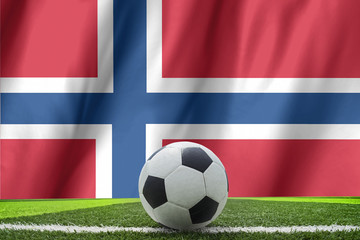 Soccer ball and national flag of Norway lies on the green grass