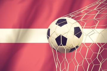 Latvia flag and soccer ball, football in goal net vintage color