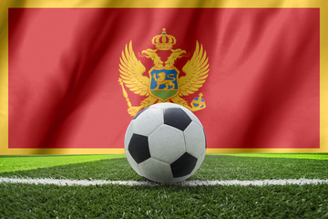 Soccer ball and national flag of Montenegro lies on the green gr