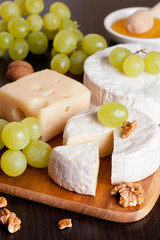 cheeses, grapes and walnuts on a wooden background