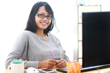 Portrait of young asian businesswoman sitting at desk in the office