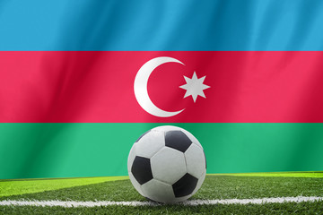 Soccer ball and national flag of Azerbaijan lies on the green gr