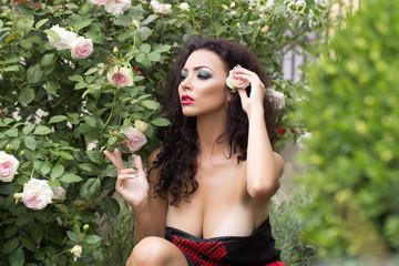 Splendid young woman posing near bush