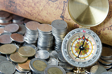 compass and coins on old map