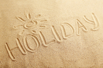 Holiday handwritten in a beach sand