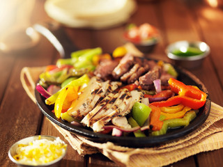 Wall Mural - mexican steak and chicken fajitas in iron skillet with bell peppers and onion shot with warm colored light