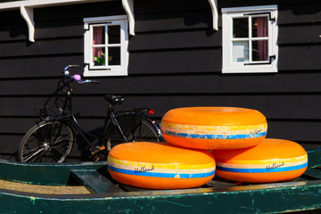 Dutch Cheese wheels on a green cart with farm house in the background