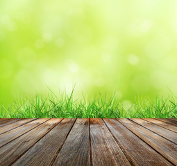 Fototapete - Wood floor with green bokeh  and  Fresh spring green grass and sunlight  . Beauty natural background