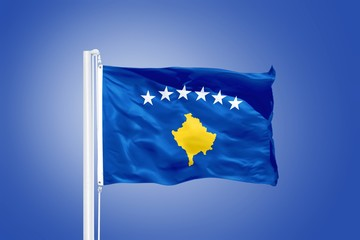 Flag of Kosovo flying against a blue sky