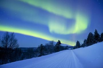 Aurora borealis over winter landscape in Finnish Lapland.