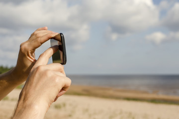People photographed on the beach using mobile phone