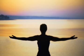 silhouette of woman taking a deep breath at the sunset
