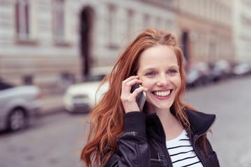 lachende frau telefoniert draußen auf der straße