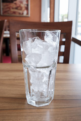 empty glass with ice cubes on wood table
