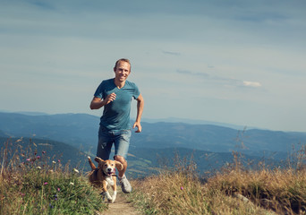 Man running with his dog on the mountain tableland.