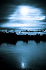 Moonlight in the clouds over a lake