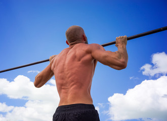 Bald man pulled on the bar against the blue sky