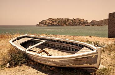 Old fishing boat and Spinalonga island, Greece.