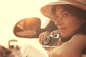 Young woman sitting in the car and holding retro photo camera at the sunset