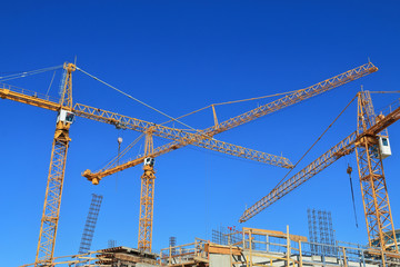 Three construction cranes and building against blue sky.