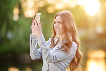 Romantic young girl holding a smartphone digital camera with her