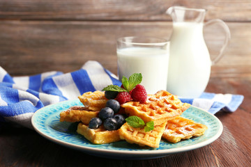 Sweet homemade waffles with forest berries and sauce on table background