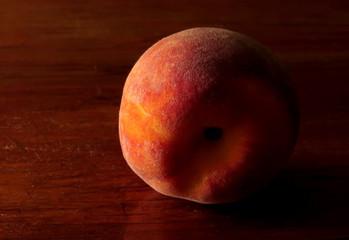 Fuzzy peach on dark table