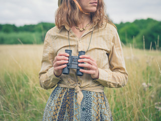 Woman with binoculars standing in meadow