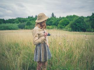 Woman with binoculars standing in meadow