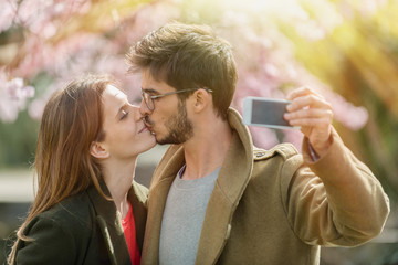 stylish young couple kissing and taking a selfie in a park