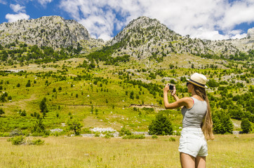 Young attractive girl taking photo of mountains landscape