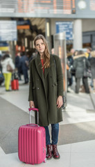 a stylish young woman in an airport about to take a plane