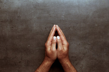 Pray, man hands on grey table background