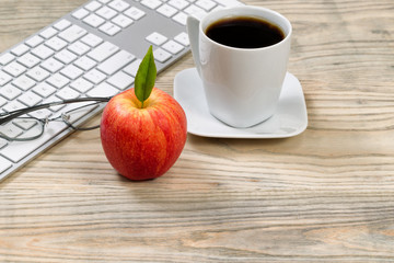 Close up of a ripe red apple for office snack on woodend desktop