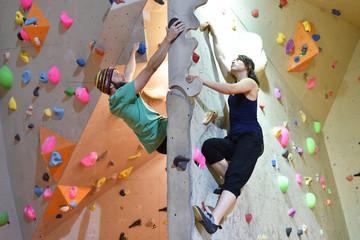 junge Frau und Mann klettern/ bouldern in einer Kletterhalle // climbing indoor