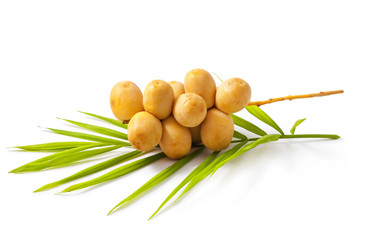A bunch of yellow raw dates with palm leaf on white background