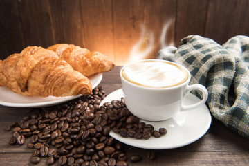 Breakfast coffee cup and croissant on wooden background