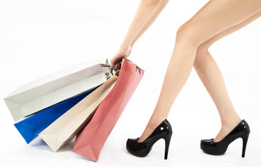 Woman legs and shopping bags .