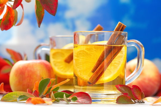 Hot drink with apple juice, lemon and cinnamon in autumn decoration