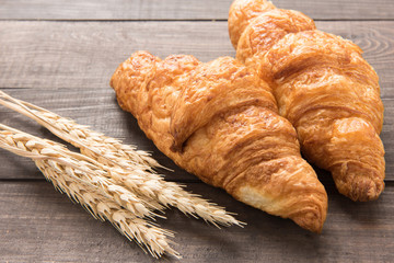 Freshly baked butter croissant on wooden background