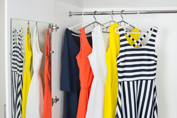 a series of bright modern fashion women's dresses on hangers in