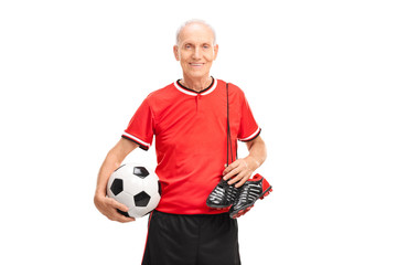 Senior gentleman in a red jersey holding a football