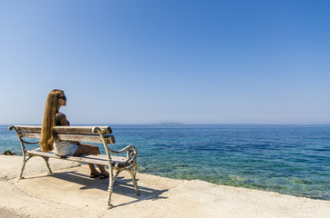 Young girl sitting on bench and looking at sea