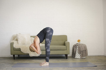 A woman practicing yoga at home