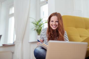 glückliche frau lernt zuhause am laptop