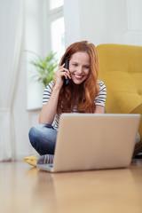 glückliche frau schaut auf laptop und telefoniert