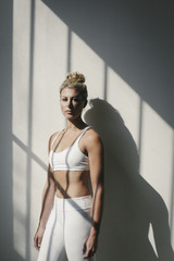 Portrait of a blonde woman, in a white crop top and leggings, standing in front of a white wall, posing for a picture.