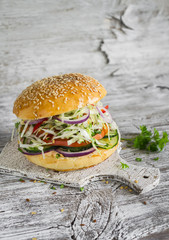 delicious veggie burger with cabbage, tomato, cucumber, onions and peppers on a light wooden surface. Healthy breakfast or snack