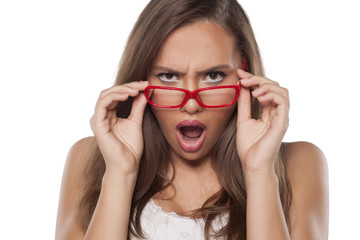 surprised beautiful girl with glasses posing on white
