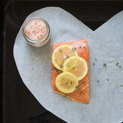 Salmon with lemon slices, thyme, pepper and Himalayan salt on heart-shaped parchment